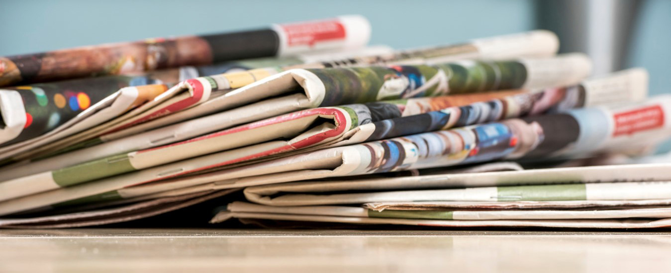 CROPPED Stack of newspapers on white wood table