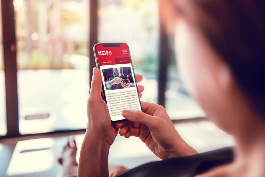 Online news on a smartphone. Woman reading news or articles in a mobile phone screen application at home. Newspaper and portal on internet.